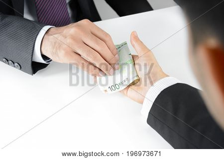 Businessman hands passing money Euro currency (EUR) - bribery concept