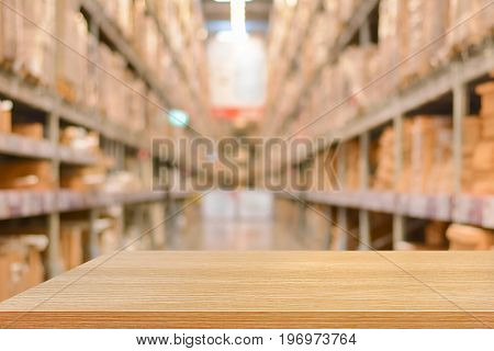 Empty wood table top or shelf on blurred warehouse background - can montage or display your products