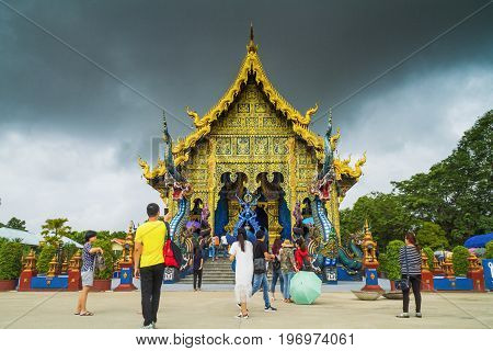 Chiang Rai Thailand - July 12 2017: Unidentified People Standing Near Sanctuary Inside Wat Rong Sua Ten Or Blue Temple At Rain Clouds Background.