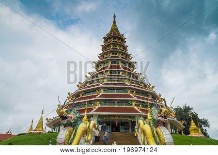Chiang Rai Thailand - July 12 2017: Unidentified People Standing Near Pagoda Statue Inside Wat Huai Pla Kang At Blue Sky Background.