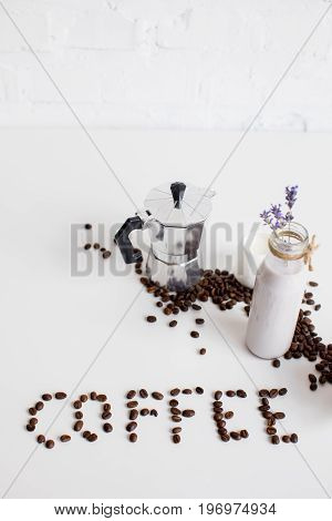 French Press, Milk Jar And Lavender Drink With Scattered Coffee Beans And Word Coffee On White Table