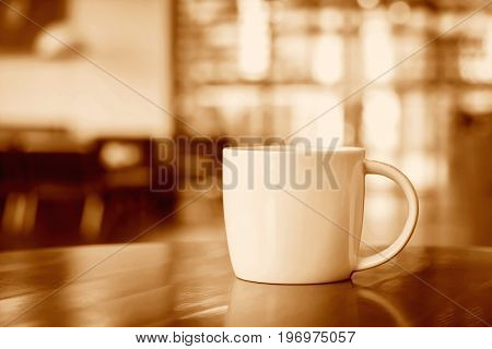 Coffee cup on the table in coffee shop - sepia tone soft focus