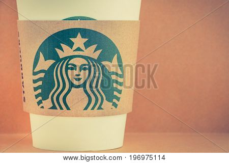 Bangkok Thailand - Mar 04 2015 : Starbucks take away coffee cup with brand logo on sleeve Starbucks is one of the most world famous coffeehouse chains from USA. - vintage tone image