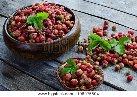 Strawberries in a wicker basket and a wooden bowl on a wooden table