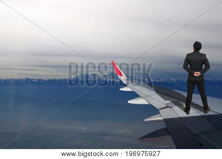 businessman standing on airplane wing which can see snow mountain Challenge business concept
