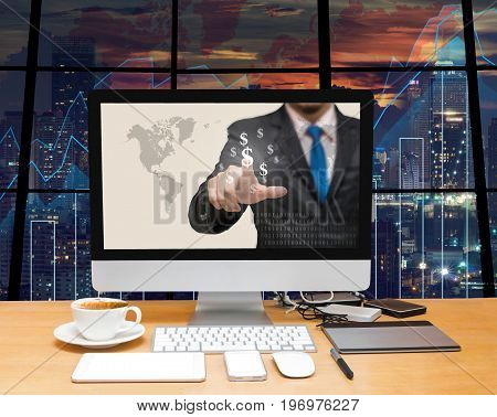Workspace with computer desktop with Businessman point sign of money at the screen on the trading graph over the blurred photo of cityscape backgroundElements of this image furnished by NASA