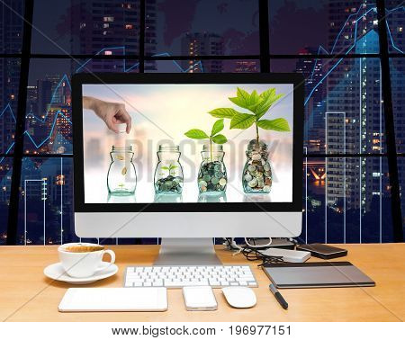 Workspace with computer desktop with Hand putting mix coins and seed in clear bottle at the screen on the trading graph over the blurred photo of cityscape background