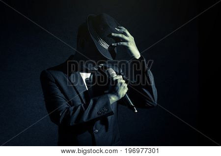 Songer hand holding the microphone and singing on black background musical concept