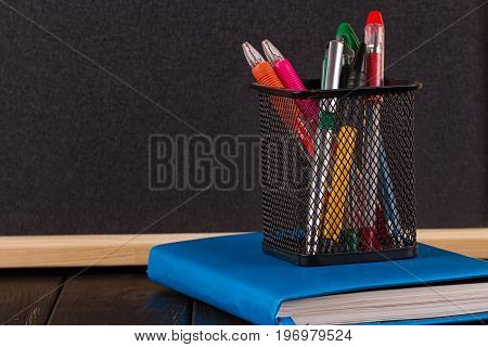 Stationery: pens pen holder diary on a black background