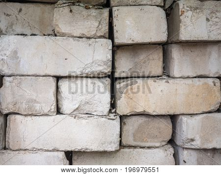 White calcium silicate bricks piled on top of each other. Old, cracked and chipped brick built, rough stack. The texture of the brick close-up.