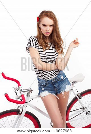 Young casual girl with flower in hair posing sensually while leaning on bicycle.