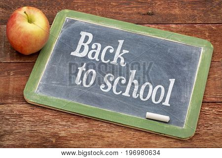 Back to school  sign -  a slate blackboard against red barn wood with an apple