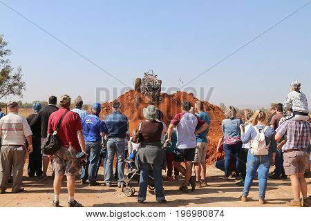 Spectators Watching Car Ascending Steep Hill, Kicking Up Sand And Stones.