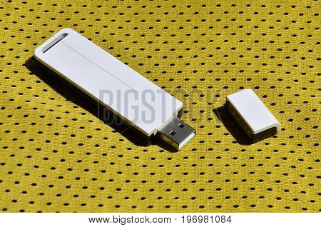 A Modern Portable Usb Wi-fi Adapter Is Placed On The Yellow Sportswear Made Of Polyester Nylon Fiber