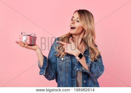 Horizontal studio shot of excited young woman holding and pointing on small gift box.