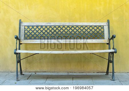 Green metal vintage bench in front of yellow backgruond wall. Wooden vintage bench against yellow blank wall.
