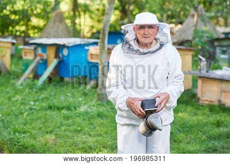 Elderly beekeeper wearing beekeeping suit standing outdoors at his apiary copyspace.