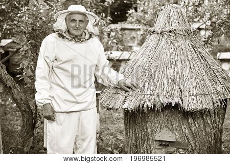 Sepia toned shot of a senior man wearing beekeeping suit standing in the garden at his apiary copyspace apiculture farming seniority professional concept.