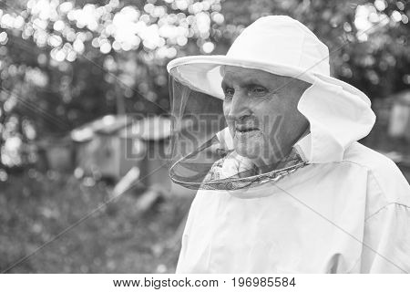 Monochrome portrait of a senior man wearing beekeeping suit smiling looking away standing outdoors at his apiary copyspace.