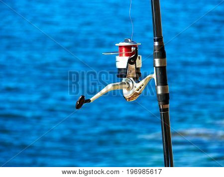 Fishing rod with a spinning reel with sea beach ocean background