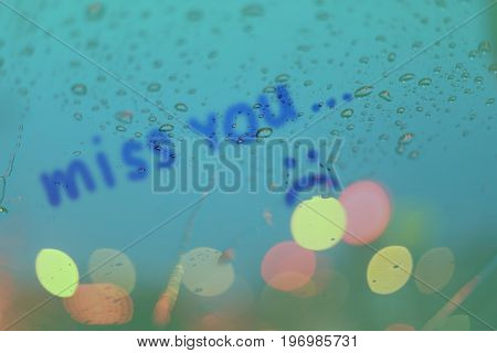 Rain drops with the word miss you write on window with light bokeh rainy season abstract background.