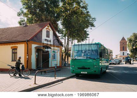 Mir, Belarus - September 2, 2016: Public Bus Car Parked Near Local Bus Station And Saint Nicolas Roman Catholic Church. Sunny Summer Day With Blue Sky
