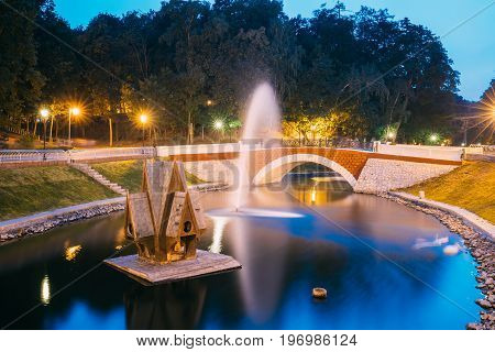 Gomel, Homiel, Belarus. Scenic View Of Park Watercourse Channel Flowing Into River Through Stone Bridge In City Park In Evening Or Night Illumination. Lighted Walkways, Greenwood Along Watercourse At Blue Hour