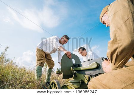 Dyatlovichi, Belarus - October 1, 2016: Reenactors Dressed As Russian Soviet Red Army Soldiers Of World War II Preparing Maxim's Machine Gun Weapon For Fight In Autumn Forest At Historical Reenactment