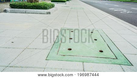 green manhole cover on the concrete footpath