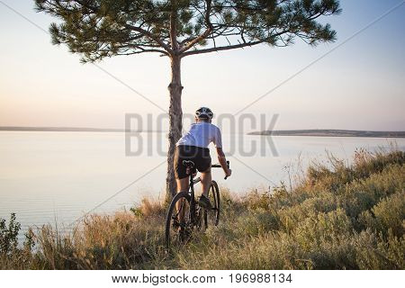 Bicycle rider on professional cyclocross bike ride downhill, pine and lake background