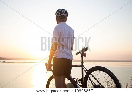 beautiful picture of cyclocross rider in helmet watching sunset or sunrise, lake and hills background