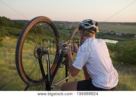 Man Adjusting and Inspecting a Bicycle outdoor on the hill