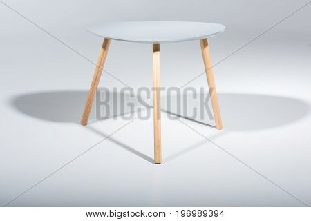 Studio Shot Of Stylish Stool With White Top And Light Wooden Legs Standing On White