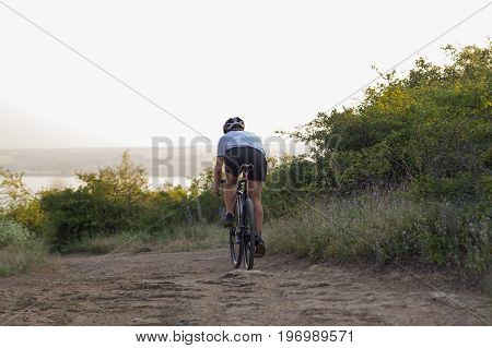 Bicycle racer ride alone on the rocky road, lake and forest background