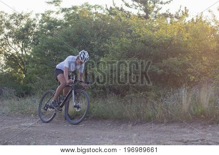 Male in helmet and sportswear on his cyclocross bike, riding on the country roads