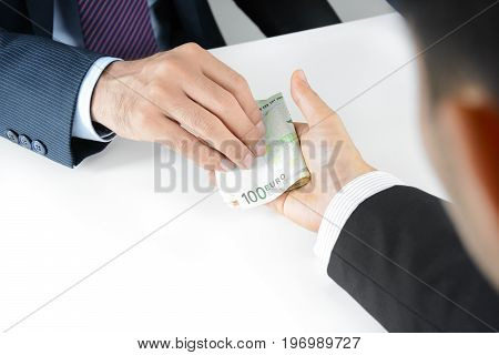 Businessman hands giving & receiving money Euro currency (EUR) - bribery concept
