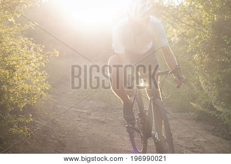 beautiful sunny photo of bicycle racer riding outdoor on the mountain road during sunrise