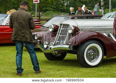 PAAREN IM GLIEN GERMANY - MAY 23 2015: A man looks at vintage car Auburn 852 Speedster. The oldtimer show in MAFZ.