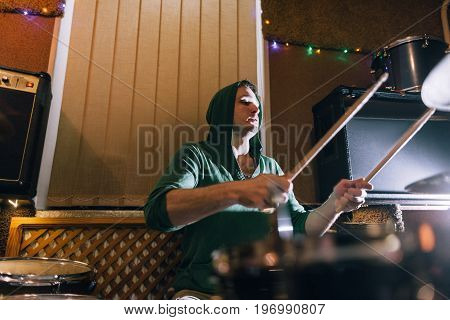 Drummer rehearsing before live concert. Male playing drums in recording studio