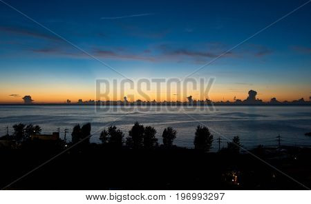 Clouds forming at the sea horizon at sunset or dusk. orange horizon with dark blue sky.