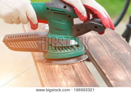 Sanding a wood with orbital sander outdoor