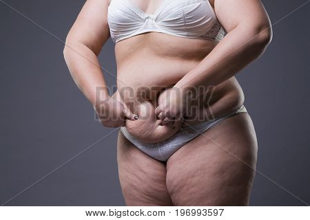Woman with fat abdomen overweight female stomach on gray studio background