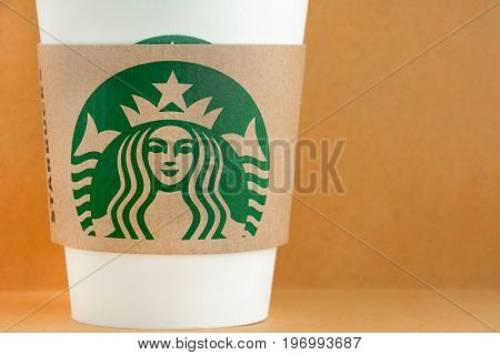 Bangkok Thailand - Mar 04 2015 : Starbucks take away coffee cup with brand logo on sleeve Starbucks is one of the most world famous coffeehouse chains from USA.