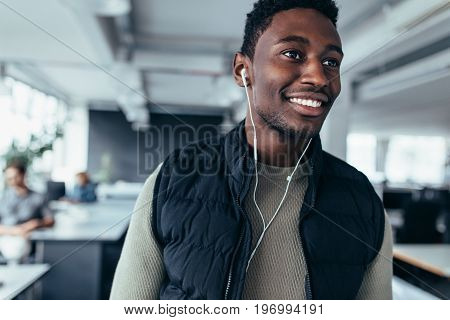 Male executive listening to music with earphones while standing in office. African young man listening music in design office.