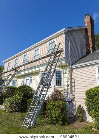 Ladders leaning on the front of a house being painted