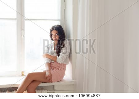 girl sits at a window in a white room and dreams