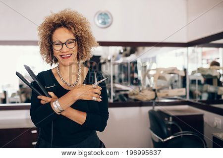 Professional hair stylist holding a hair straightener and scissors. Woman hairdresser in happy mood at the salon.