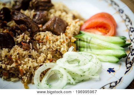Uzbek pilaf with beef on a wooden background