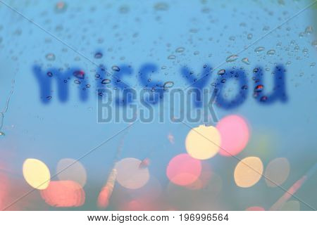 Rain drops with miss text write on window with light bokeh rainy season abstract background.