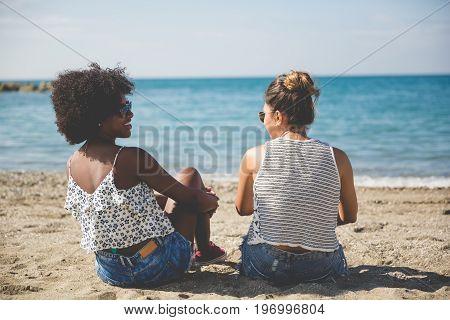 Two Women Relaxing On Beach Talking